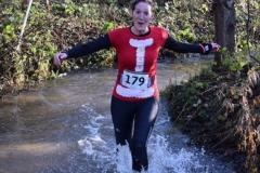 Sara running through river at Pudding Race