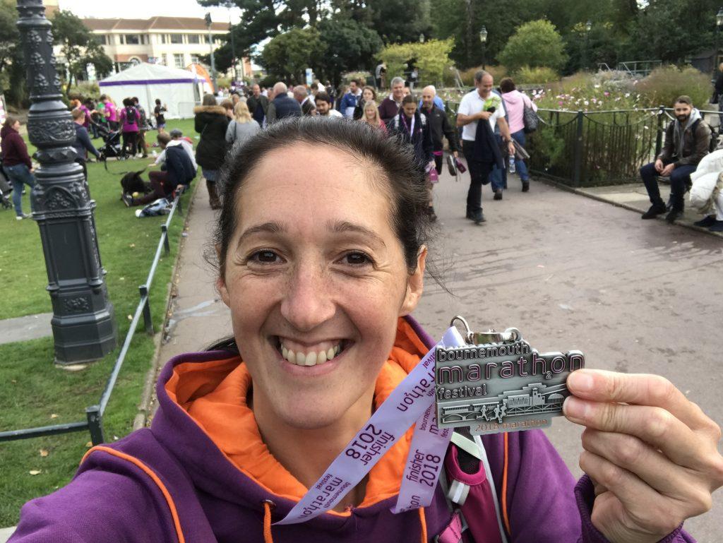 Sara and her bournemouth marathon medal in Bournemouth gardens