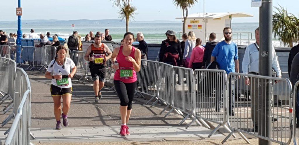 Sara running the bournemouth marathon towards bournemouth pier