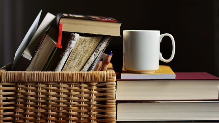 What Exactly Is Self-Care - Pile of book and a coffee cup