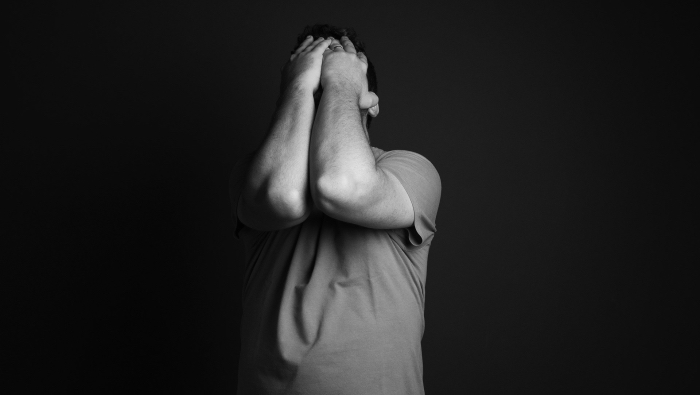 Anxiety or Excitement - man clutching his face with his hands
