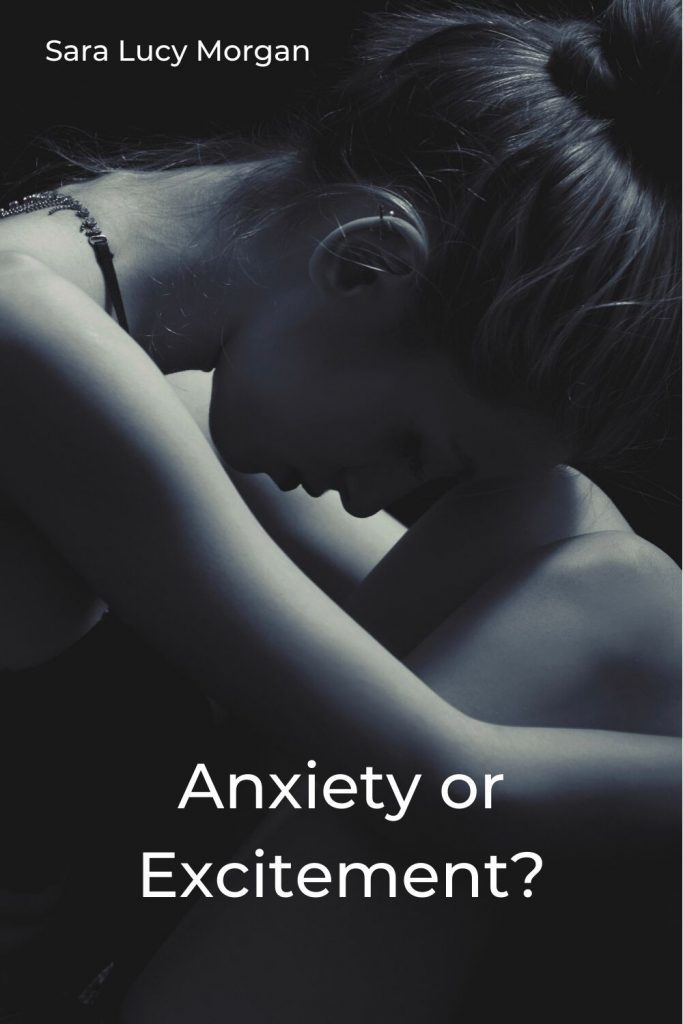Anxiety or excitement - Woman sat hugging her knees and resting her head on them.