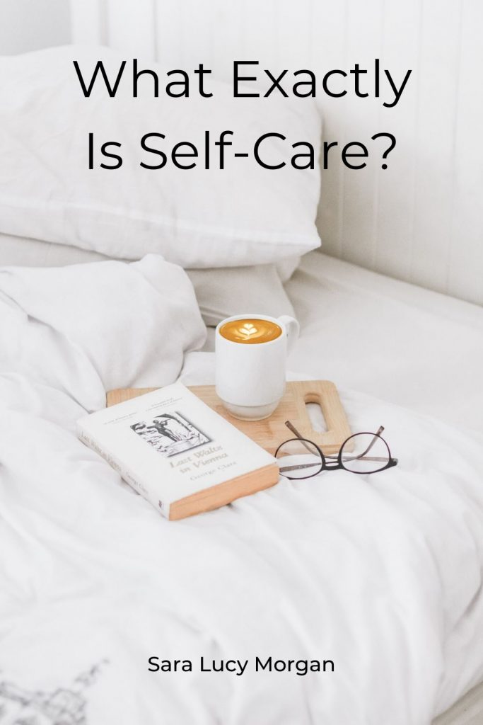 What exactly is self-care - bed with book and a cup of coffee along with reading glasses